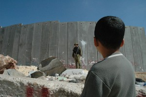boy_and_soldier_in_front_of_israeli_wall.jpg